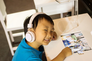 Asian kid play computer internet games and wear headset