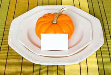 Autumn Thanksgiving dinner table setting with decorative pumpkin