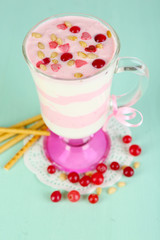 Cranberry milk dessert in glass  on color wooden background