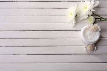 Beautiful flowers and skin cream on wooden background