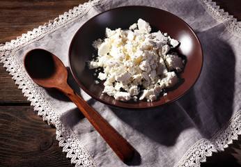 Cottage cheese on plate on lace napkin on wooden background