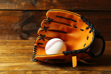 Baseball ball in glove on wooden background