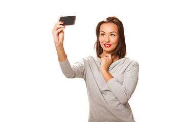 Beautiful young woman taking selfie.