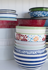 Pile of old dishes and bowls on a white shelf