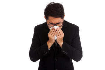 Asian businessman caught cold. Sneezing into tissue.