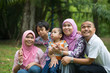 Happy Malay Asian Family enjoying family time together in the pa