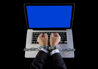 Hands of businessman addicted to work chain to computer