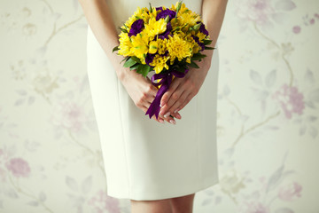 Bride's hands with wedding bouquet of violet and yellow flowers