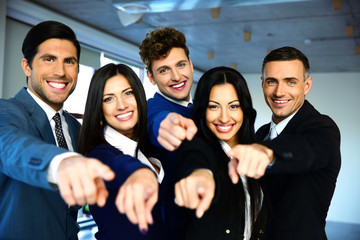 Group of a cheerful business people poiting on the camera