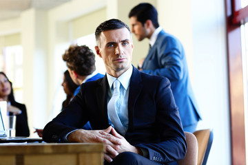 Confident businessman sitting at the table