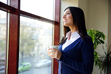 businesswoman standing with cup of coffee in office