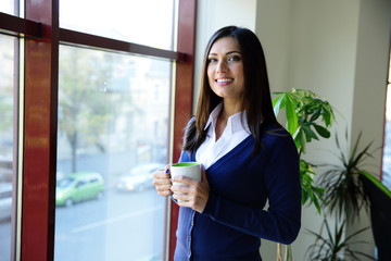 Happy young businesswoman standing with cup of coffee in office