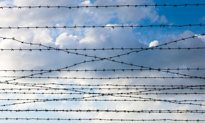 Barbed wire against the cloudy sky background