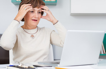 Surprised woman looking at computer screen with hands on head