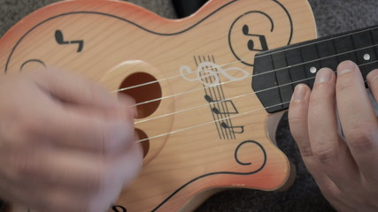 Plays in a child's guitar. Closeup.