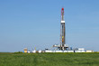 land oil drilling rig on green wheat field - 73036110
