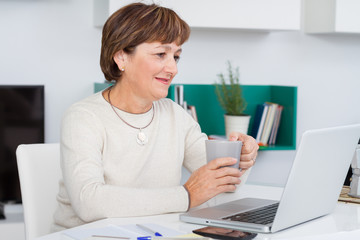 Woman looking computer screen with cap of coffee