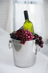 Wine bottle in metal bucket with grapes