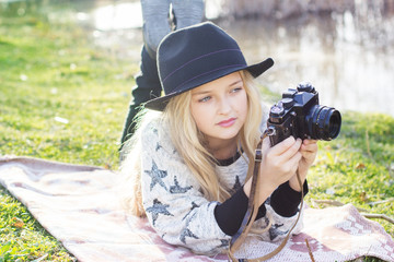 Cute little girl is resting near lake with camera