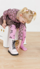 little girl putting on boots