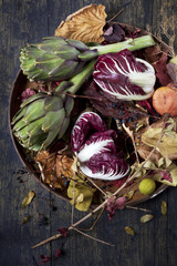 raw artichokes and fresh red chicory with colored dry leaves
