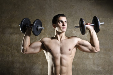 Young man lifting weights, shoulders exercises