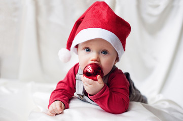 Funny baby in Santa Claus cap with a Christmas ball
