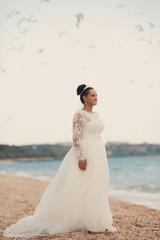 Beautiful bride on the beach in wedding dress