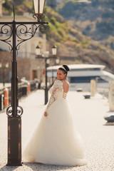 Beautiful bride walking on the street in wedding dress