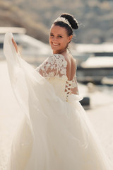 Beautiful bride walking on the street in wedding dress