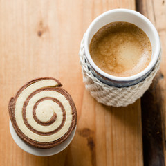 Cappuccino with heart made of cocoa powder and crocheted mug