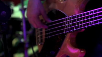 Bass-guitarist play in a nightclub closeup
