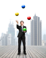 businessman throwing and catching colorful balls