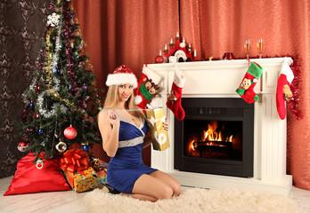 beautiful woman near the fireplace selebrating christmas