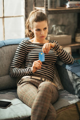 Portrait of thoughtful young woman with credit card