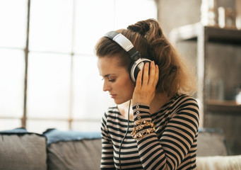 Portrait of young woman listening music in headphones