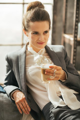 Business woman with coffee latte relaxing in loft apartment