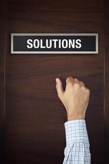 Hand is knocking on Solutions bureau door
