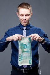 Young businessman is knitting a ruble banknote.