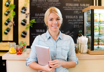 The owner of small restaurant holding a digital tablet