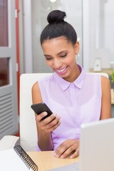 Businesswoman text messaging at office desk