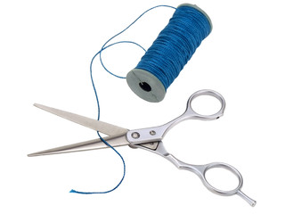 ..scissors and a spool of blue thread on white background