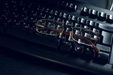glasses on a black keyboard and Office desk
