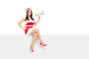 Female Santa holding a megaphone seated on a panel