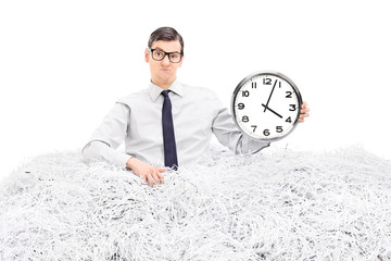 Man holding a clock in a pile of shredded paper