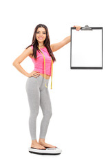Woman standing on weight scale and holding a clipboard