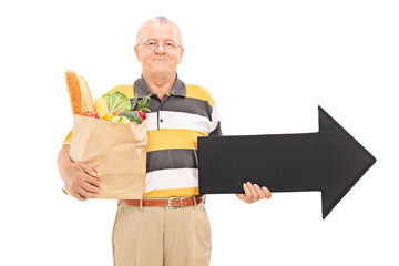 Mature man holding a grocery bag and an arrow
