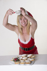 Woman in Santa outfit puts icing sugar topping onto Mince Pies