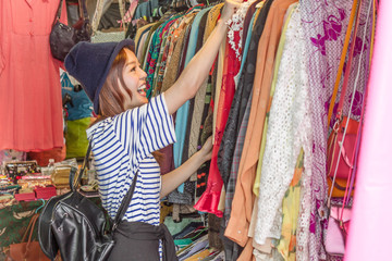 Asian woman looking at clothes on rack
