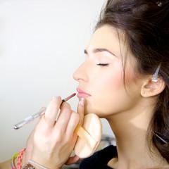 Female model getting makeup before photo shoot